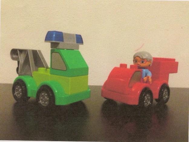 Legot ja legodublot ovat mieluisimpia leluja, joita käytän niin töissä kuin kotonakin oman lapseni kanssa. Legoilla saa aikaan monipuolisia ja mielikuvituksellisia leikkihetkiä, jotka sopivat melkein tilanteeseen kuin tilanteeseen. Rauhallisempana tekemisenä rakentelemme ohjeen mukaan ja siinä ohessa  tulee harjoiteltua esimerkiksi käsitteitä (värit, määrät, sijainnit ym ), kuulomuistia jne. Rakentelu ilman ohjetta puolestaan kehittää luovuutta ja siinä pääsee lapsikin ohjaamaan ja neuvomaan aikuista. Rakenteluhetken jälkeen aletaan varsinaiseen leikkiin, jossa toimijoina ovat itserakennetut autot tai valmiit legohahmot. Leikin edetessä rakennetaan lisää tarpeen mukaan. Kuvassa olevat legot liittyvät leikkiin, jossa mummu pelasti paloautollaan (lapsen tekemä ilman ohjetta) koiran jyrkänteelle tippuvasta autosta ja hinausauto (ohjeen mukaan rakennettu) hinasi rikkinäisen auton korjaamolle.